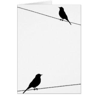 Siluetas del pájaro en el alambre tarjeta