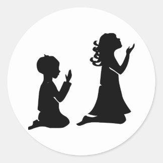 Siluetas negras de rogación de los niños pegatinas redondas