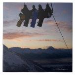 Siluetean a cuatro snowboarders en un remonte azulejo cuadrado grande