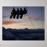 Siluetean a cuatro snowboarders en un remonte posters