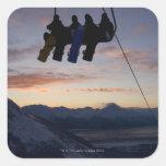 Siluetean a cuatro snowboarders en un remonte pegatina cuadrada