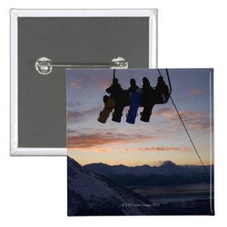 Siluetean a cuatro snowboarders en un remonte pin cuadrado