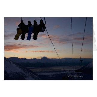 Siluetean a cuatro snowboarders en un remonte tarjetas