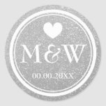 """Silver glitter monogram wedding favor stickers<br><div class=""""desc"""">Round faux silver glitter and white monogram wedding favor stickers. Cute heart with monogrammed name initials of bride and groom plus date of marriage. Personalized thank you stickers or luxurious envelope sealers / seals. Elegant typography for bride and groom name initials. Chic border design / fancy design. Customizable background color....</div>"""