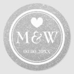 "Silver glitter monogram wedding favor stickers<br><div class=""desc"">Round faux silver glitter and white monogram wedding favor stickers. Cute heart with monogrammed name initials of bride and groom plus date of marriage. Personalized thank you stickers or luxurious envelope sealers / seals. Elegant typography for bride and groom name initials. Chic border design / fancy design. Customizable background color....</div>"