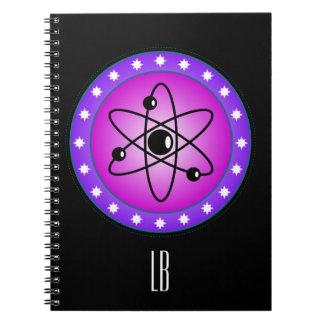 Símbolo atómico personalizado en un fondo rosado libros de apuntes con espiral