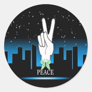 Símbolo de paz de la mano con un fondo de la pegatina redonda