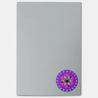 Símbolo del átomo en un fondo rosado post-it® nota