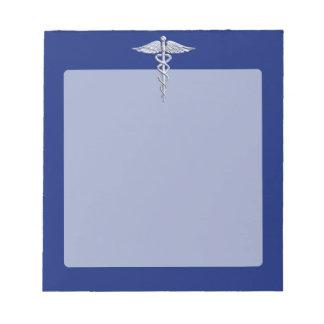 Símbolo médico del caduceo de plata del cromo en blocs de papel