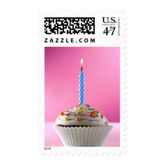Single lit candle in iced cup cake decorated postage