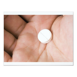 Single white pill in palm card