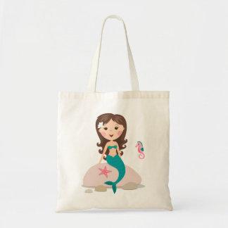 Sirena linda que se sienta en una roca con el bols bolsas lienzo