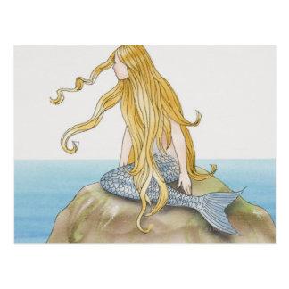 Sirena rubia que se sienta en la roca del mar vis postal