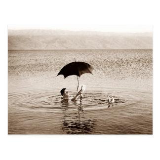 Sirva la lectura debajo del paraguas en el mar postal