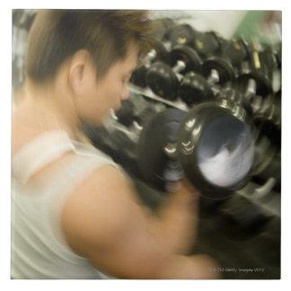 Sirva la pesa de gimnasia de elevación en gimnasio azulejo cuadrado grande