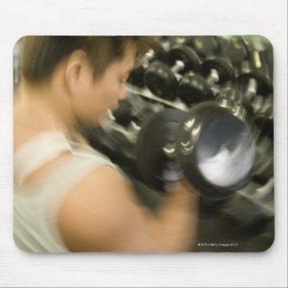 Sirva la pesa de gimnasia de elevación en gimnasio tapete de raton