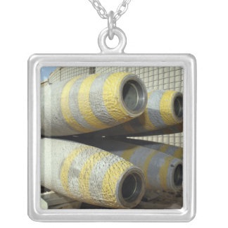 Six GBU-12 bombs sit in a rack Necklaces