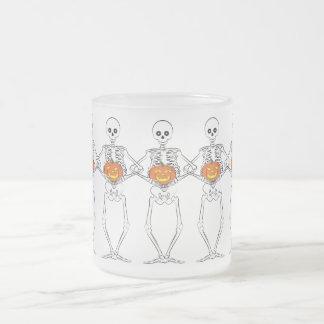 Skeletons holding pumpkins frosted glass coffee mug