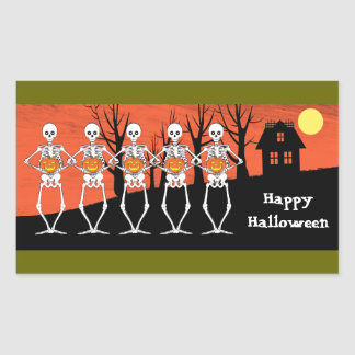 Skeletons holding pumpkins with a haunted house in rectangular sticker