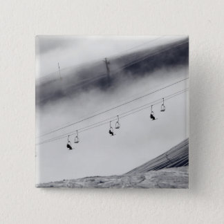 Skiers on a chair lift button