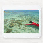 Skindiver swimming in a tropical sea mouse mats