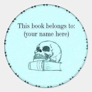 Skull and a book, light blue round sticker