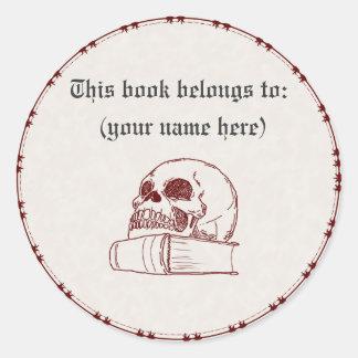 Skull and a book round sticker