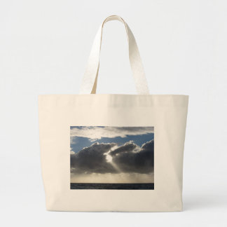 Sky with giants cumulonimbus clouds and sun rays large tote bag