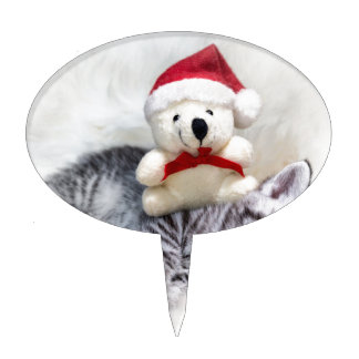 Sleeping young tabby cat with christmas bear cake topper