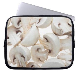 Sliced button mushrooms (agaricus bisporus), on laptop computer sleeves