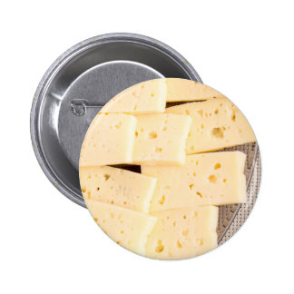 Slices dry hard yellow cheese on a plate closeup pinback button