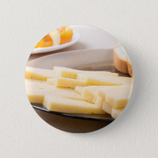 Slices of cheese and bread on a plate closeup pinback button