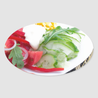 Slices of fresh raw vegetables oval sticker