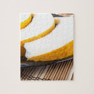 Slices of juicy yellow melon on a black plate jigsaw puzzle
