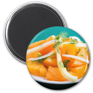 Slices of orange tomato on a plate with onions magnet