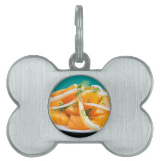 Slices of orange tomato on a plate with onions pet tag