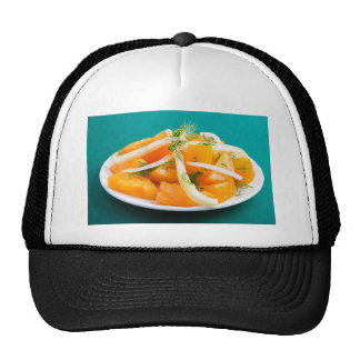 Slices of orange tomato on a plate with onions trucker hat