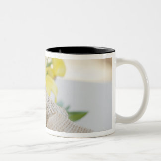 Slippers beside a wooden bowl with yellow lilies Two-Tone coffee mug