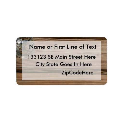 Small glass on wooden brown fishing dock planks address label