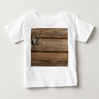 Small glass on wooden brown fishing dock planks shirts