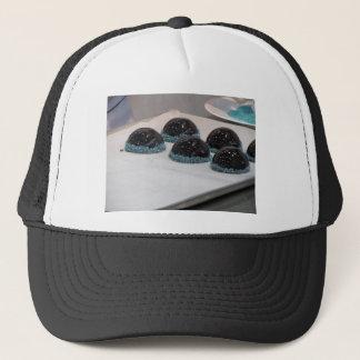 Small glazed chocolate cakes with hazelnut grains trucker hat