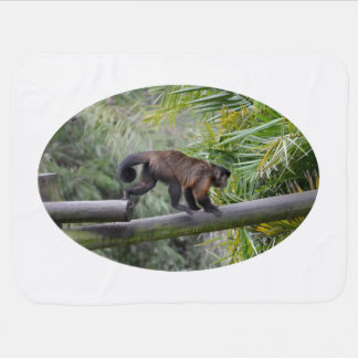 small monkey running across railing baby blanket