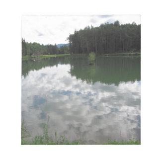 Small mountain lake with reflections of clouds notepad