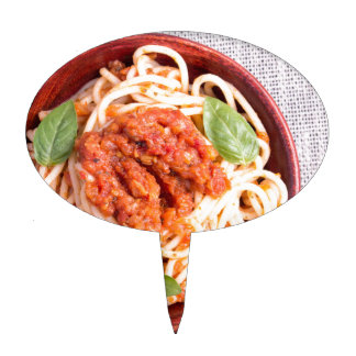 Small portion of cooked spaghetti with tomato cake topper