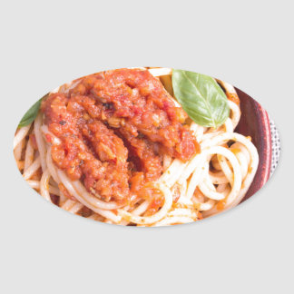 Small portion of cooked spaghetti with tomato oval sticker