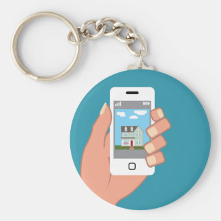 Smartphone in hand with house picture keychain