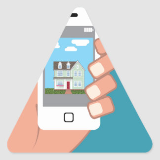 Smartphone in hand with house picture triangle sticker