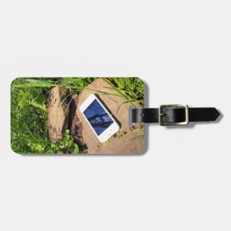 Smartphone on a rock in a meadow bag tag