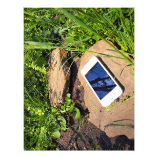 Smartphone on a rock in a meadow letterhead