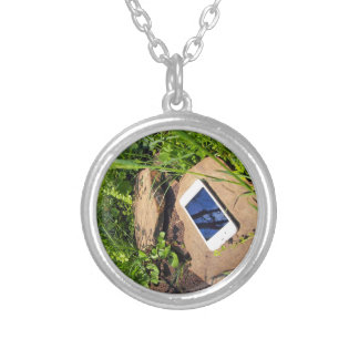 Smartphone on a rock in a meadow round pendant necklace